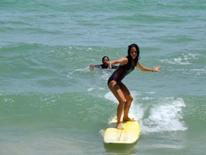 Girl Surfing With Instructor
